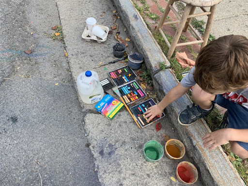 Artists of all ages join each other to create temporary masterpieces. Although the rain will soon wash them away, the beautiful colors consume the entire street.