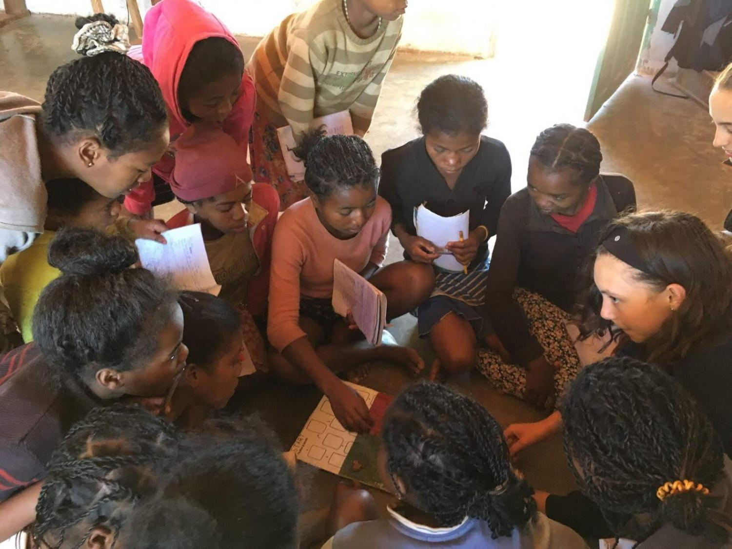Emma uses a board game to teach numbers and colors in English to students in Madagascar.